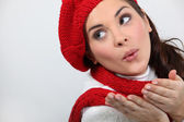 A woman wearing winter clothes is blowing a kiss — Stok fotoğraf