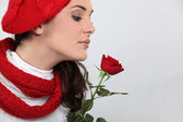 Woman in knitted hat smelling rose — Stock Photo