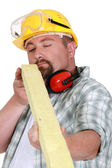 Worker eyeing a piece of wood — Stock Photo