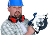 Tradesman holding a circular saw — Stock Photo