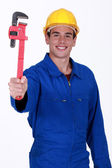 Young workman in jumpsuit holding adjustable spanner — Stock Photo