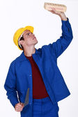 Young bricklayer in jumpsuit inspecting brick — Stock Photo