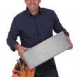 Cheerful builder with a concrete block — Stock Photo #16310711