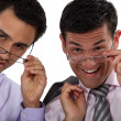 Duo of executives with glasses lowered - Stock Photo