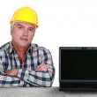 Artisan resting on concrete wall with computer — Stock Photo #16317661