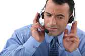 Businessman struggling to hear his headset — Stock Photo