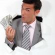 Man with banknotes of paper coming out of hole - Stock Photo