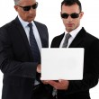 Businessmen wearing sunglasses and looking at a laptop — Stock Photo #16332921