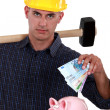 Royalty-Free Stock Photo: Laborer putting bills in a piggy bank