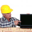 Senior craftsman pointing at his laptop - Stock Photo