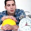 Builder being woken up by alarm clock — Stock Photo