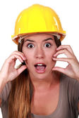 A horrified female construction worker. — Stock Photo