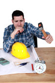 Engineer hitting an alarm clock with a hammer — Stock Photo