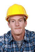 A portrait of a construction worker biting his lips. — Stock Photo