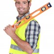 Happy worker resting spirit-level on shoulder — Stock Photo #16346659