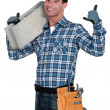 Young bricklayer holding concrete block — Stock Photo #16349321