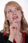 Woman wondering and holding her chin — Stock Photo