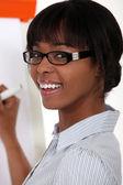 Woman with glasses writing on blackboard — Stock Photo