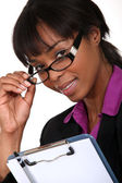 Businesswoman peering over her glasses — Stock Photo
