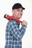 Cheerful man with an adjustable wrench — Stock Photo
