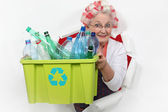Old lady recycling plastic bottles — Stock Photo