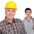 Stock Photo: Mature craftsmwith apprentice