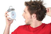 Man screaming with alarm clock in hand — Stock Photo