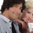 Couple drinking from the same cup with straws - ストック写真