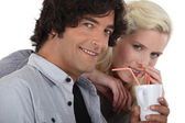 Couple drinking from the same cup with straws — Stock Photo