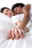 Young couple asleep holding hands in bed — Stock Photo