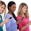 Stock Photo: Three young women using their mobile telephones