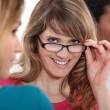 Stock Photo: Young wompeering over her glasses