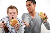 Friends eating hamburgers and watching a football game — Stock Photo