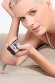 Closeup of a woman with a remote control — Stock Photo