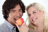 Woman looking at man eating an apple — Stock Photo