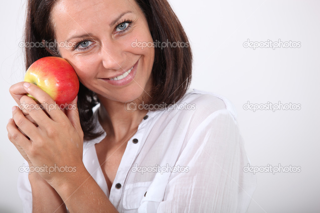 Smiling woman holding an apple to her face  Stock Photo #16434803