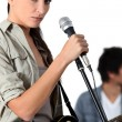 Stock Photo: Young woman singer holding microphone