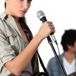 Young woman singer holding microphone — Stock Photo