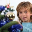 Prepubescent boy decorating a Christmas tree — Stock Photo