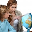 Boy and girl looking at a globe — Stock Photo #16455379