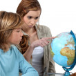 Boy and girl looking at a globe — Stock Photo