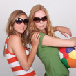 Two teenagers wearing sunglasses holding beach ball — Stock Photo