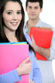 Two students carrying folders — Stock Photo