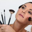 Woman holding various make-up brushes — Stock Photo #16460129