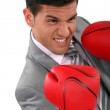 Young businessman wearing boxing gloves — Stock Photo