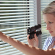 Stock Photo: Spy peering through some blinds