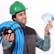 Plumber holding his wages - Stock Photo