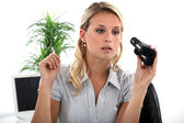 Young blond office worker with pair of binoculars — Stock Photo