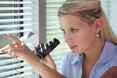 Office worker looking out of a window with binoculars — Stock Photo