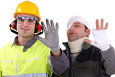 Injured tradesman comparing his hand to a healthy colleague — Stock Photo